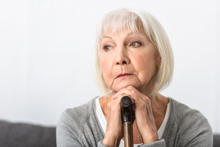 pensive senior woman with wooden cane looking away at home Stock Photo