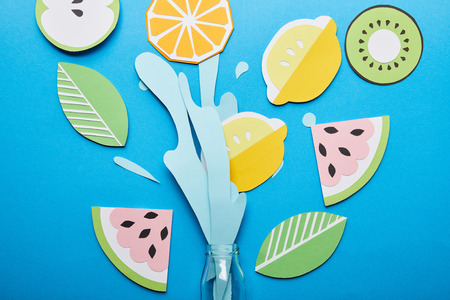 top view of paper cut water splash with fruits near glass bottle on blue background Banco de Imagens