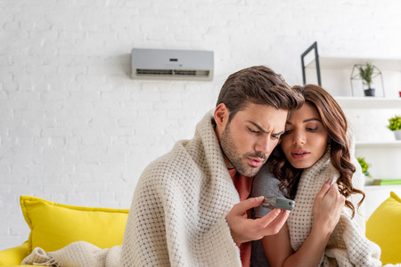 handsome man holding remote control while warming under blanket with pretty girlfriend at home