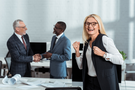 selective focus of happy businesswoman celebrating triumph near multicultural businessmen shaking hands in office Imagens
