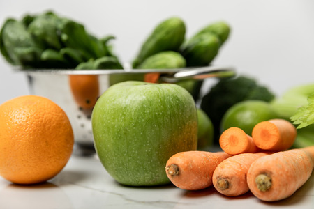 selective focus of green apple, orange and carrots near green cucumbers on white Stock Photo
