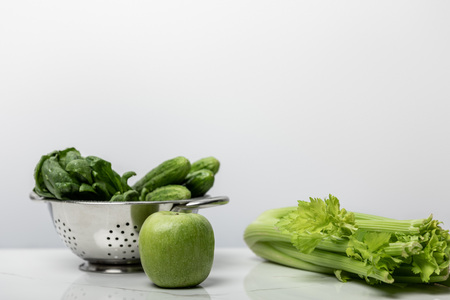 green apple near fresh vegetables and spinach leaves on white Stock Photo