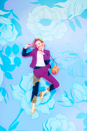 Top view of businesswoman in suit and high-heeled shoes talking on telephone while lying on blue background with floral illustration Stock Photo