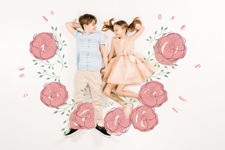 Top view of cheerful kids holding hands near pink flowers on white background. 스톡 콘텐츠