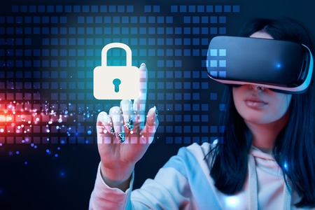 Selective focus of young woman in virtual reality headset pointing with finger at glowing cyber security illustration on dark background 스톡 콘텐츠
