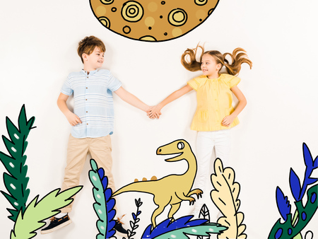 Top view of cheerful kids holding hands near dinosaur on white background.