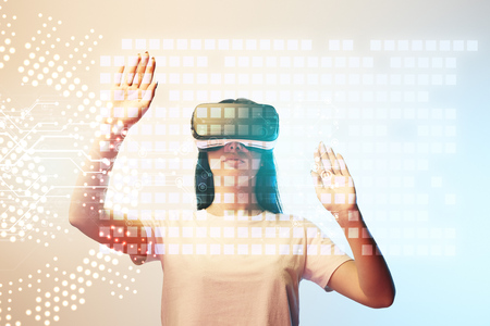 Young woman in virtual reality headset pointing with hands at glowing data illustration on beige and blue background Stock Photo