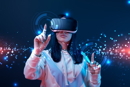 Woman in virtual reality headset pointing with fingers at glowing cyber illustration on dark background Stock fotó