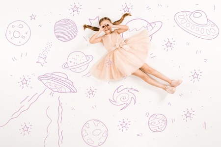 Top view of cheerful kid in pink dress with hands near eyes in space on white background. 스톡 콘텐츠