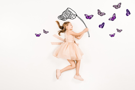 Top view of cheerful kid in pink dress holding butterfly net near butterflies on white background.