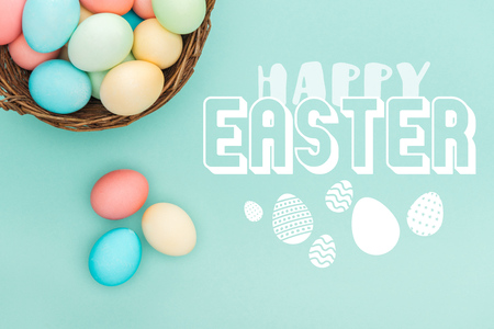 Top view of multicolored painted eggs in wicker basket with happy Easter lettering on blue background