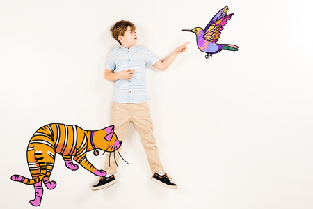 Top view of surprised kid pointing with finger humming bird near orange cat on white background.