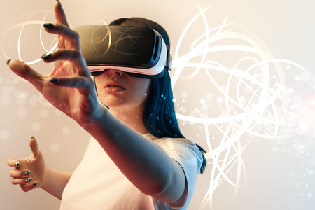 Young woman in virtual reality headset gesturing among glowing cyber illustration on beige and blue background