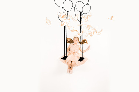 Top view of cheerful kid in pink dress on swing near birds and balloons on white background.