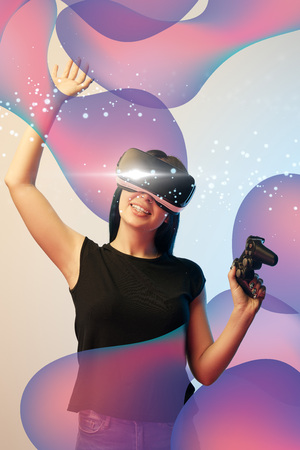 Happy young woman in virtual reality headset with joystick in hands on beige and blue background with abstract glowing illustration