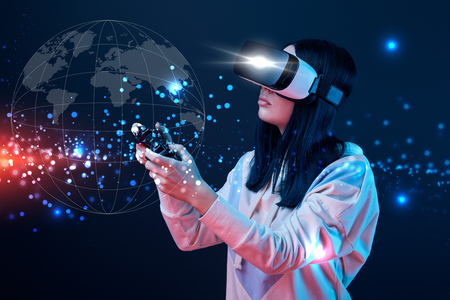 Young woman in virtual reality headset using joystick on dark background with globe illustration 写真素材