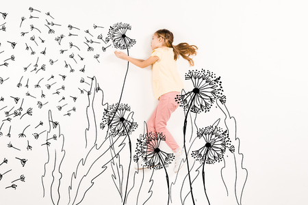 Top view of kid blowing dandelion seeds while flying on white background. 스톡 콘텐츠