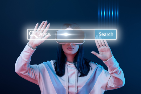 Young woman in virtual reality headset gesturing near glowing search bar illustration on dark background Stock Photo