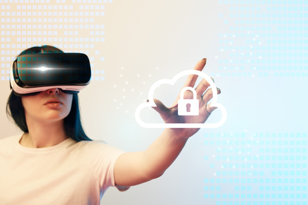 Young woman in virtual reality headset pointing with hand at internet security illustration on beige and blue background