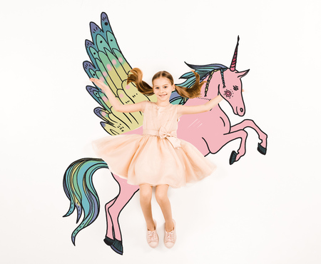 Top view of cheerful kid looking at camera and gesturing near unicorn on white background.