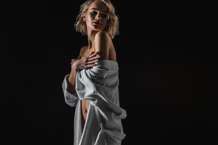 Beautiful young woman in white bathrobe posing isolated on black background with copy space