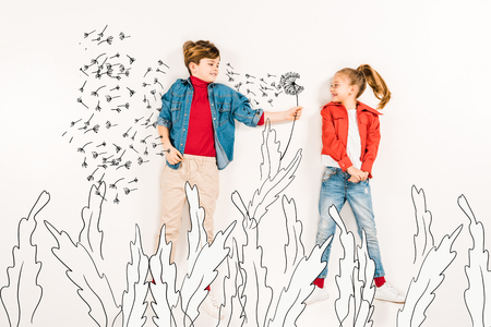 Top view of happy kid gesturing near friend and dandelion seeds on white background.