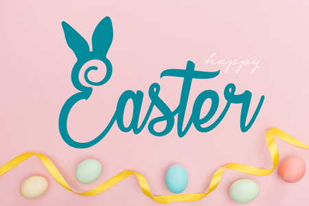 Top view of painted multicolored chicken eggs and satin ribbon on pink background with happy Easter blue lettering
