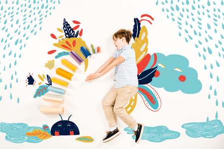 Top view of surprised kid near colorful books and fairy characters on white background.