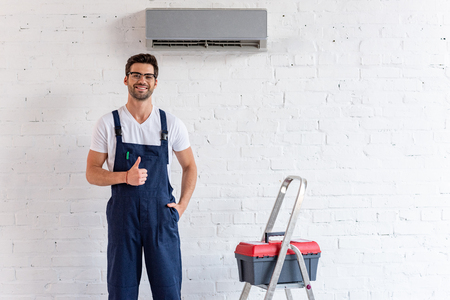 cheerful repairman showing thumb up while standing under air conditioner near stepladder and toolbox
