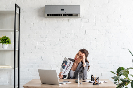 Attractive businesswoman waving newspaper while sitting at workplace under air conditioner