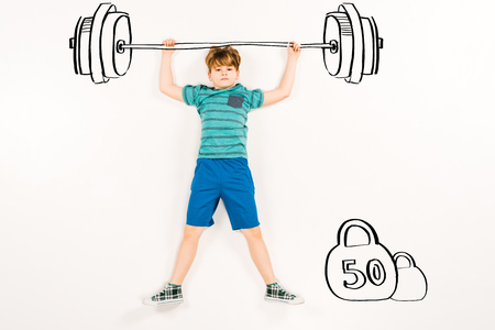 Top view of cute kid holding barbell and looking at camera on white background