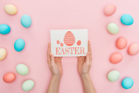 Cropped view of woman holding greeting card with Easter lettering near multicolored painted chicken eggs on pink background 스톡 콘텐츠