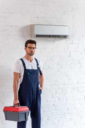 Serious repairman in overalls holding toolbox and looking at camera while standing under air conditioner