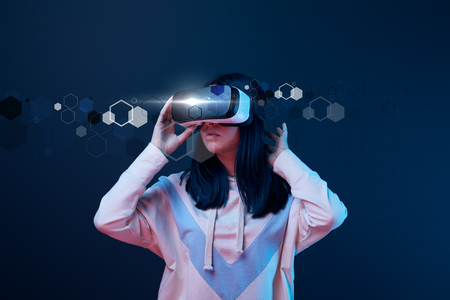 Young woman in virtual reality headset among cyber illustration on dark background