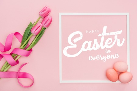 Top view of pink tulips bouquet with ribbon and painted eggs near frame with white happy Easter to everyone lettering on pink background
