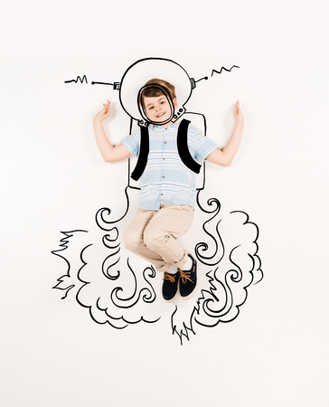 Top view of cheerful kid in astronaut suit gesturing on white background