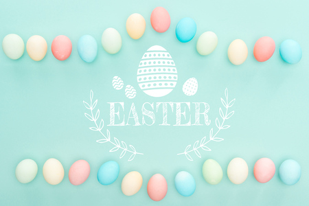 Top view of painted chicken eggs on blue background with Easter illustration