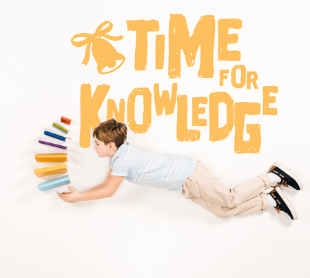 Top view of kid holding books and flying near time for knowledge lettering on white background