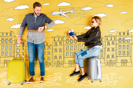 Happy woman holding passports and tickets while man with suitcase checking time with city and airplane illustration on yellow background Standard-Bild - 124381973