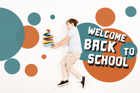 Top view of child near colorful books and welcome back to school lettering on white background