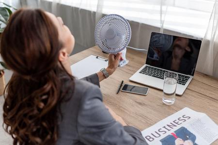 Joven empresaria que sufre de calor mientras está sentado en el lugar de trabajo en la oficina