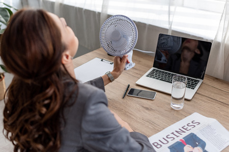 Young businesswoman suffering from heat while sitting at workplace in office