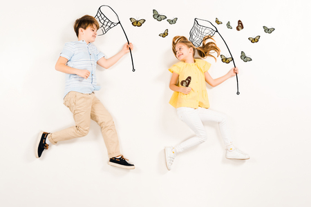 Top view of cheerful kids with butterfly nets smiling near butterflies on white background