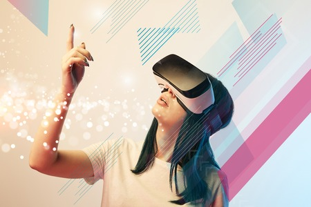Young woman in virtual reality headset pointing with finger at glowing abstract illustration on beige background