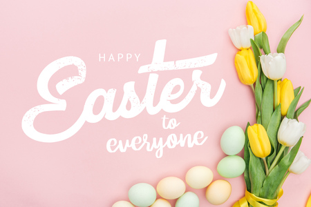 top view of painted chicken eggs and bright tulips on pink background with happy Easter to everyone lettering