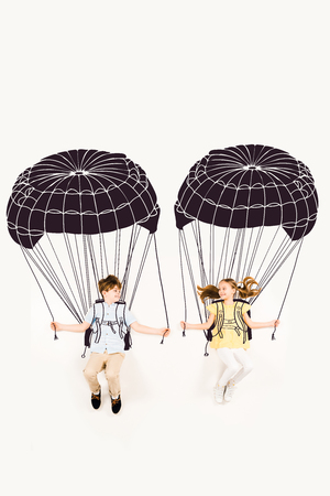 Top view of cheerful boy and happy girl holding parachutes while flying on white background
