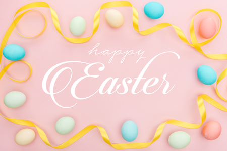 Top view of painted multicolored chicken eggs and satin ribbon on pink background with happy Easter lettering Stock Photo