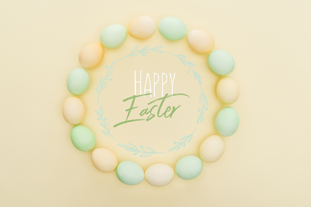 Top view of round frame made of painted chicken eggs on light yellow background with happy Easter lettering inside Stockfoto