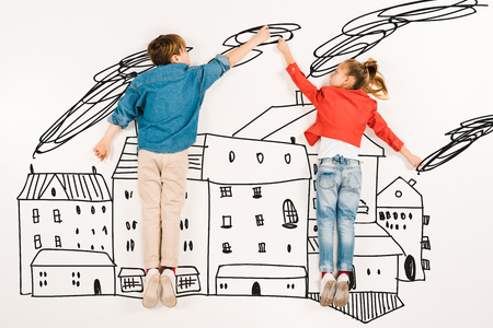Top view of cute children gesturing while flying near houses on white background