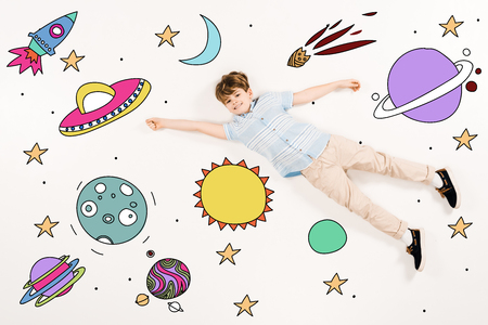 Top view of cheerful kid flying in space on white background